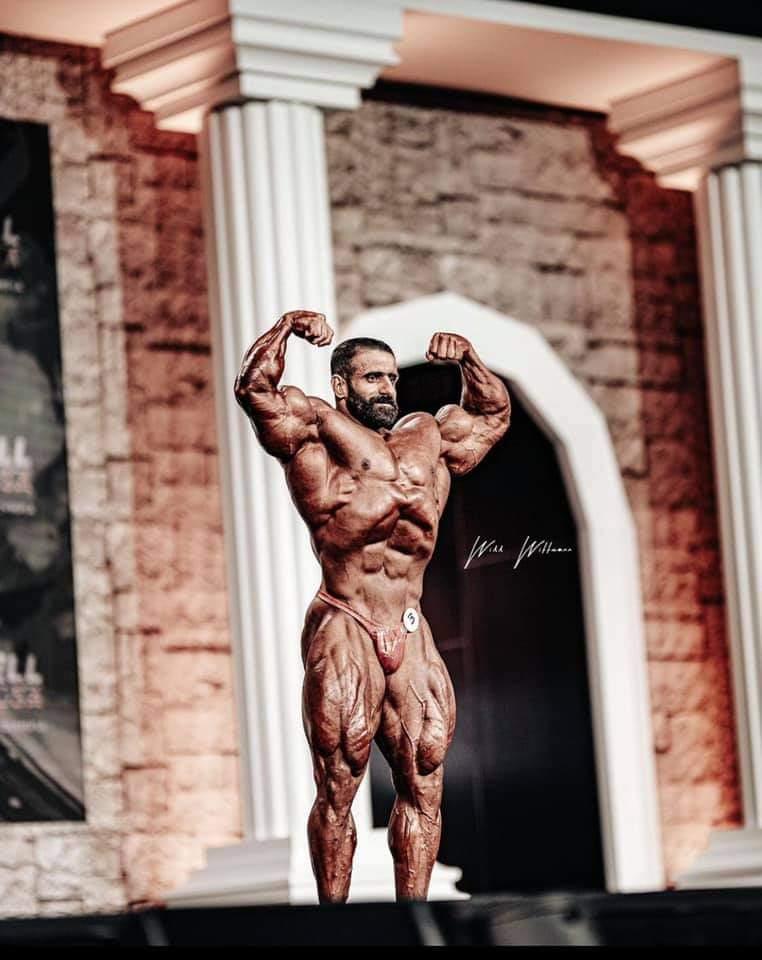 hadi choopan sul palco del mister olympia 2020 durante il pregara posa di doppi bicipiti frontali