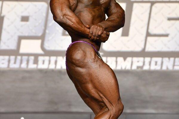 Christopher Robinson posa di side chest sul palco del NPC USA CHAMPIONSHIPS 2020